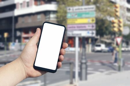 Mockup of the smartphone in the man hand, with a white screen on the background of urban buildings and street signs. Template for mobile navigation application