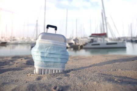 Time to travel. The concept of safe rest during a pandemic Covid-19 Coronavirus. Suitcase for travel with a medical mask on the beach against the background of a sea of sunny sky and yachts
