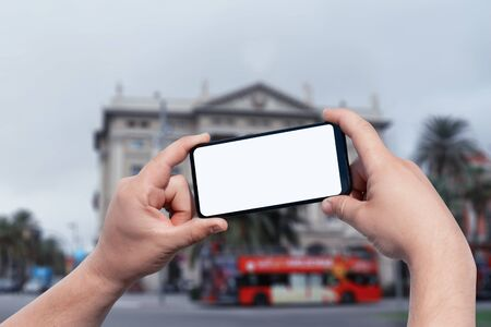 Mockup of the smartphone in the man hands, with a white screen on the background of a tourist bus on a city street. Tourism and travel online Reklamní fotografie