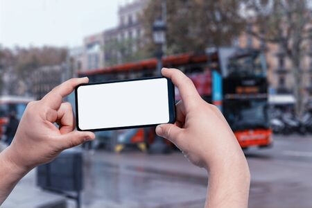 Mockup of the smartphone in the man hands, with a white screen on the background of a tourist bus on a city street. Tourism and travel online 免版税图像