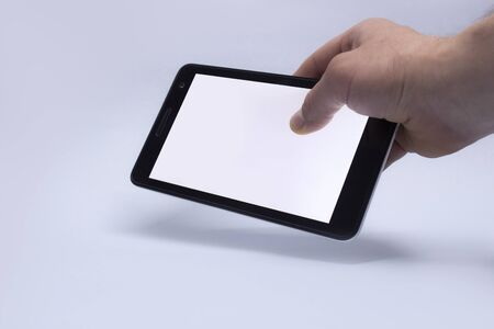 Man hand on light background holds Tablet with isolated screen. Mockup Technology