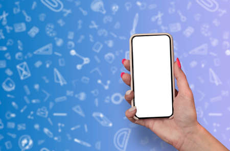 Back to School concept. Woman Hand holding the black Mockup smartphone with beautiful nails on the background with stationery icons. Mobile device isolated on purple colour