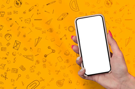 Back to School concept. Woman Hand holding the black Mockup smartphone with beautiful nails on the background with stationery icons. Mobile device isolated on orange colour