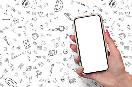 Back to School concept. Woman Hand holding the black Mockup smartphone with beautiful nails on the background with stationery icons. Mobile device isolated on white colour Foto de archivo