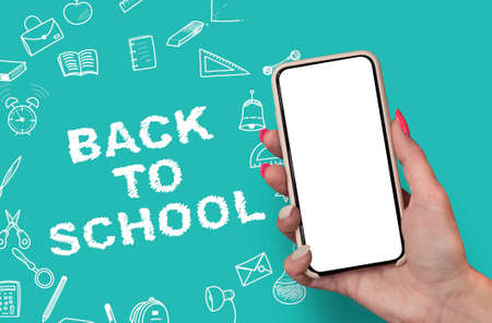 Back to School concept. Woman Hand holding the black Mockup smartphone with beautiful nails on the background with stationery icons. Mobile device isolated on green colour