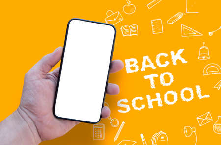Back to School concept. Man Hand holding the black Mockup smartphone with beautiful nails on the background with stationery icons. Mobile device isolated on orange colour