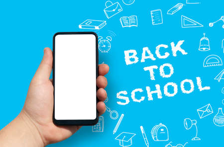 Back to School concept. Man Hand holding the black Mockup smartphone with beautiful nails on the background with stationery icons. Mobile device isolated on blue colour