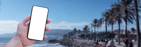Time to travel. Smartphone in hand, against the background of the sea and the city under a sunny sky. Mock-up Technology 免版税图像