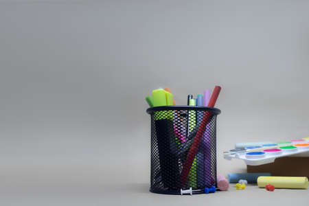 Paints for painting and stationery in the basket. Back to school background