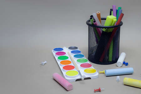 Back to school background. Paints for painting and stationery in the basket