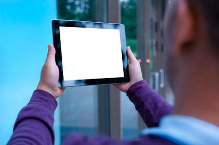 Mockup image of a Man holding black tablet in hand with blank white screen on background in the door 免版税图像