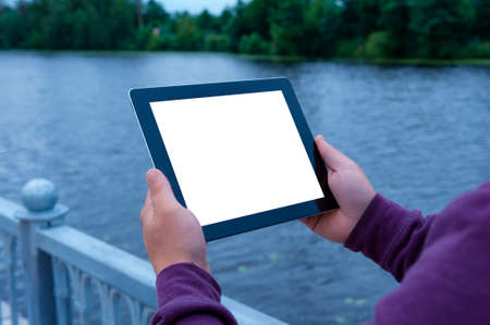 Mockup image of a Man holding black tablet in hand with blank white screen on background river 免版税图像