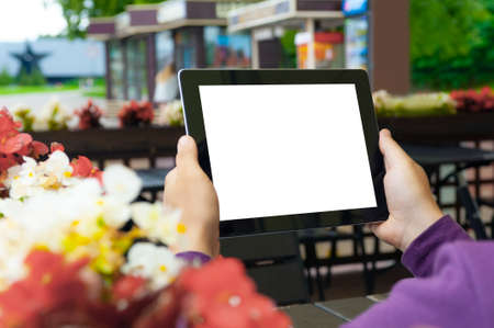 Mockup image of a Man holding black tablet in hand with blank white screen on background in cafe 免版税图像