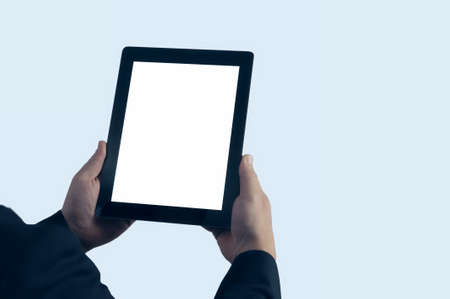 Mock up technology. Businessman in blue jacket is holding a tablet with a white screen on a light background 免版税图像