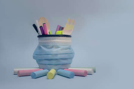 Back to school background. Crayons for drawing and stationery in the basket with a medical mask against the virus COVID-19 免版税图像