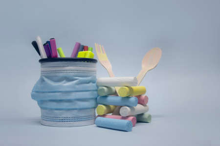 Crayons for drawing and stationery in the basket with a medical mask against the virus COVID-19. Back to school background