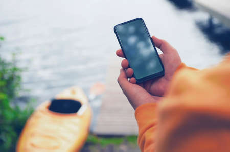 The guy holds a portable charger with a smartphone in his hand. A man against the background of water and a kayak charges the telephone with Power Bank. Concept on the theme of tourism 免版税图像