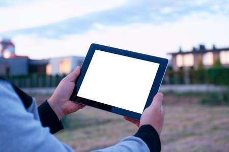 Mock up of a tablet with white screen in hand, against the background of modern houses