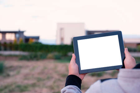 Mock up of a tablet with white screen in hands, against the background of modern houses 免版税图像