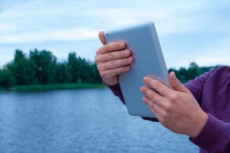 Mock up image of a Man holding black tablet in hand on background river 免版税图像