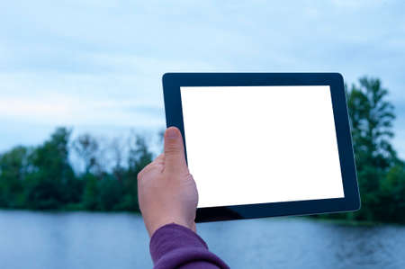 Mock up image of a Man holding black tablet in hand with blank white screen on background river