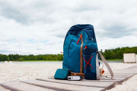 Portable travel charger. Power Bank charges a musical bluetooth speaker against a backdrop of journey bags, a beach, a lake and a forest with clouds. Concept on the theme of tourism