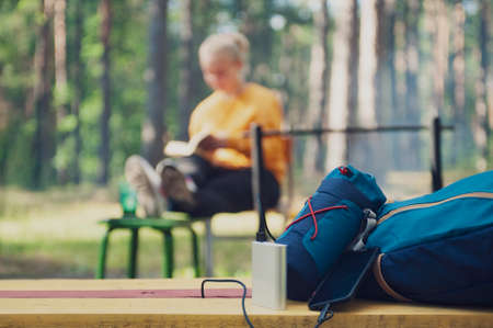 Portable Charger in Camping. Girl tourist reading a book in the woods on the background of a backpack and bank turn. Travel concept with technology