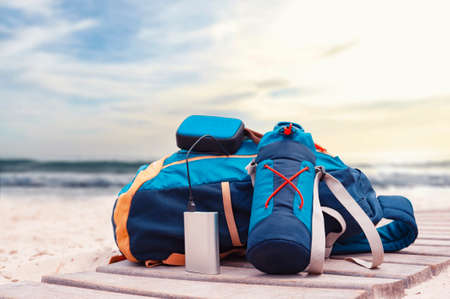 Portable travel charger. Power Bank charges a musical speaker against a backdrop of journey bags, a beach and sea with sky. Concept on the theme of tourism 免版税图像