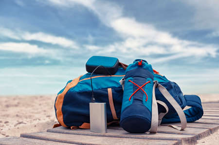 Portable travel charger. Power Bank charges a musical speaker against a backdrop of journey bags, a beach and sky with cloud. Concept on the theme of tourism 免版税图像