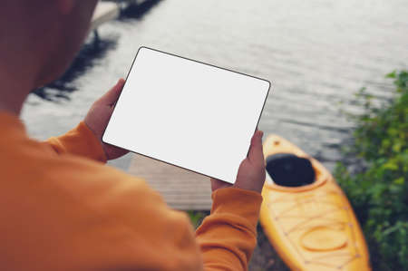 The tourist holds a phone in his hands. Mock up smartphone close-up on the background of a kayak and a lake. Concept on the topic of tourism and recreation