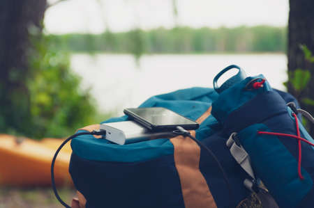 Portable travel charger. Power Bank charges Smartphone against a backdrop of journey bags, a lake and forest. Concept on the theme of tourism