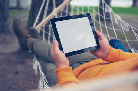 Man lies and rests in a hammock with a mock-up of a tablet with a white screen in his hands