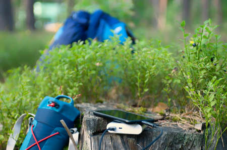 Portable travel charger. Power Bank charges Smartphone against a backdrop of journey bags and forest. Concept on the theme of tourism 免版税图像