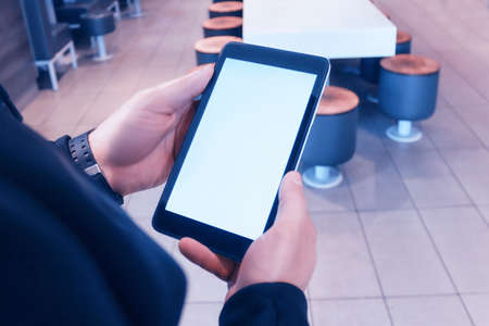 Mock-up a man holds in his hands a tablet with a white screen, on a cafe background