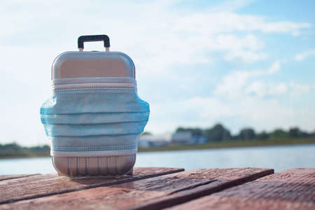 Time to travel. The concept of safe rest during a pandemic Covid-19 Coronavirus. Suitcase for travel with a medical mask on the beach against the background of the river and the sunny sky