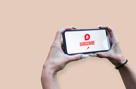 Woman Hand holding the black Mockup smartphone with a close up icon with beautiful nails. Blogger asks to subscribe to his channel for video vlogs. Mobile device isolated on light background