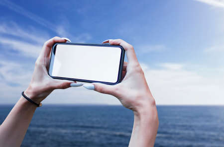 Girl holds in his hand a smartphone close-up, with a white screen on a background of sea. Mock-up Technology 免版税图像