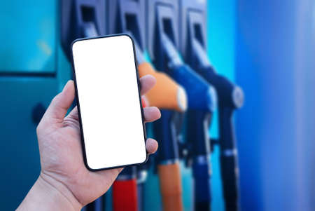 Mock up smartphone in hand closeup on the background of a gas station. Payment refueling online