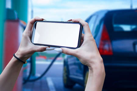 Mock up smartphone in hand closeup on the background of a gas station with car. Payment refueling online