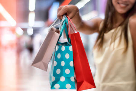 Young woman in a dress walks in the supermarket with beautiful and bright gift bags in her hands