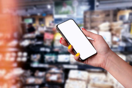 Girl with beautiful nails holds a Mockup smartphone. White display in her hands close-up against the background of a store counter with groceries