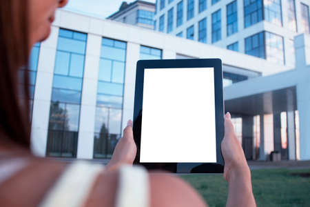 Young woman demonstrates the screen white screen tablet close-up. Mock up on the background of a modern business center 免版税图像