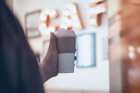 Cup of coffee in the hands of a guy in a cafe against the background of a luminous signboard. Mockup of a cardboard eco mug