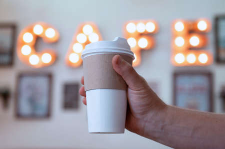 Cup of coffee in the hands of a guy in a cafe against the background of a luminous signboard. Mock-up of a cardboard eco mug Banco de Imagens