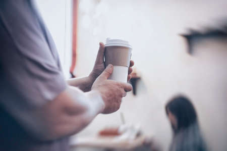 Man holds in his hand a mockup of an ecological paper cup for coffee in a restaurant 免版税图像 - 153648179
