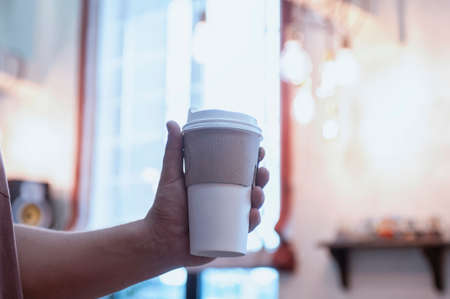 Man holds in his hand a mockup of an ecological paper cup for coffee in a restaurant