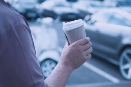 Man holds an ecological cup with coffee in his hand. Mock up paper cup on the background of a parking lot with a vintage motor scooter and a car