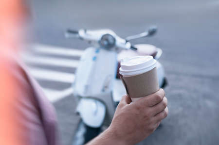 Mock-up of a cardboard glass for coffee in a man's hand against the background of a vintage motor scooter
