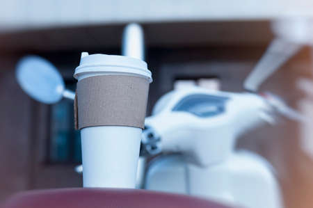 A man holds an ecological cup with coffee in his hand. Mock up paper cup on the background of a motor scooter Banco de Imagens
