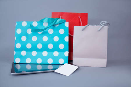 Online shopping concept. Close-up tablet mockup with white screen and credit card against the background of bright gift bags